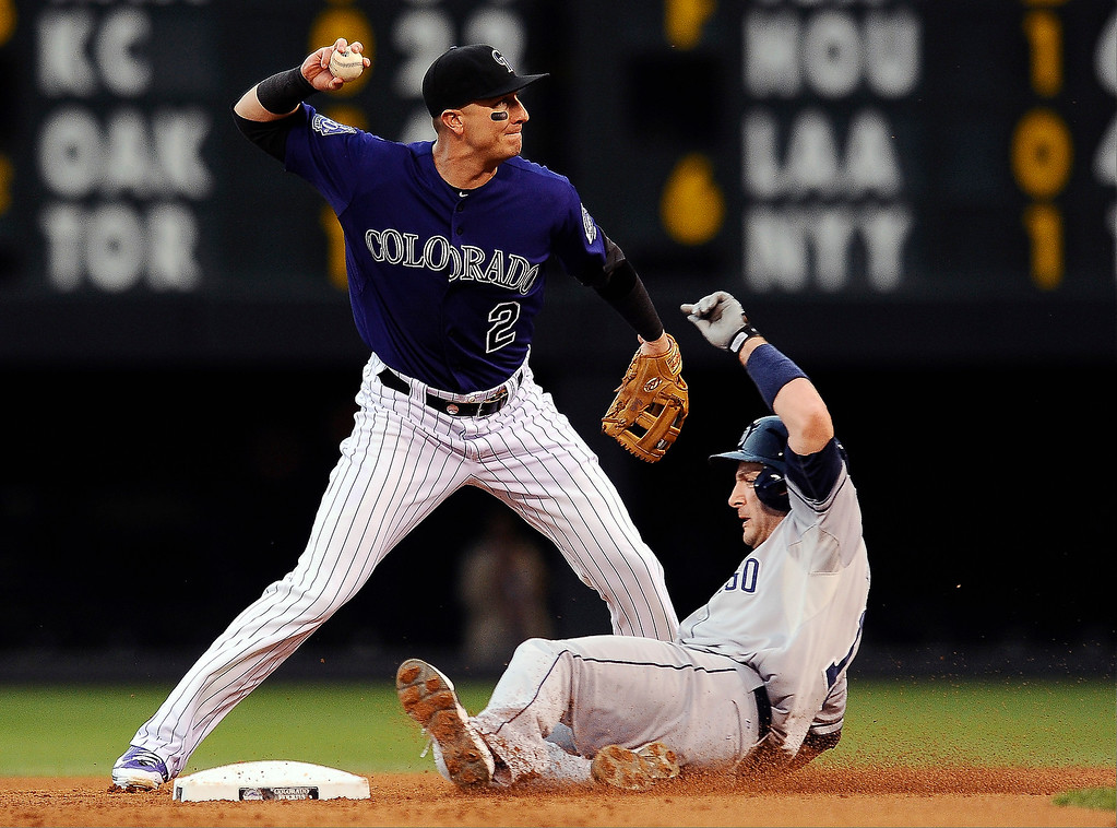 . Colorado Rockies shortstop Troy Tulowitzki forces out San Diego Padres Chris Denorfia at second base and tries unsuccessfully to throw to first for the double play in the first inning of a baseball game on Monday, Aug. 12, 2013 in Denver. (AP Photo/Chris Schneider)