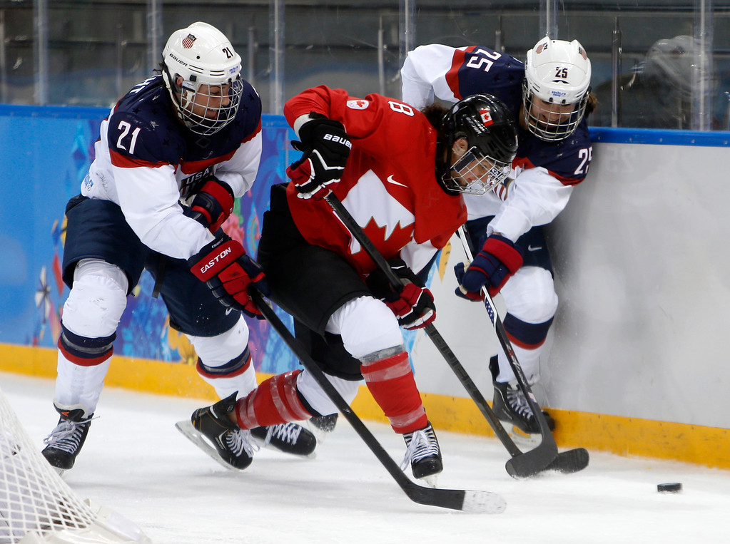. USA\'s Hilary Knight (21) and USA\'s Alex Carpenter (25) fight for the puck against Canada\'s Laura Fortino (8) in the third period for their preliminary round at the Shayba Arena for the 2014 Winter Olympics in Sochi, Russia on Wednesday, Feb. 12, 2014.  (Nhat V. Meyer/Bay Area News Group)