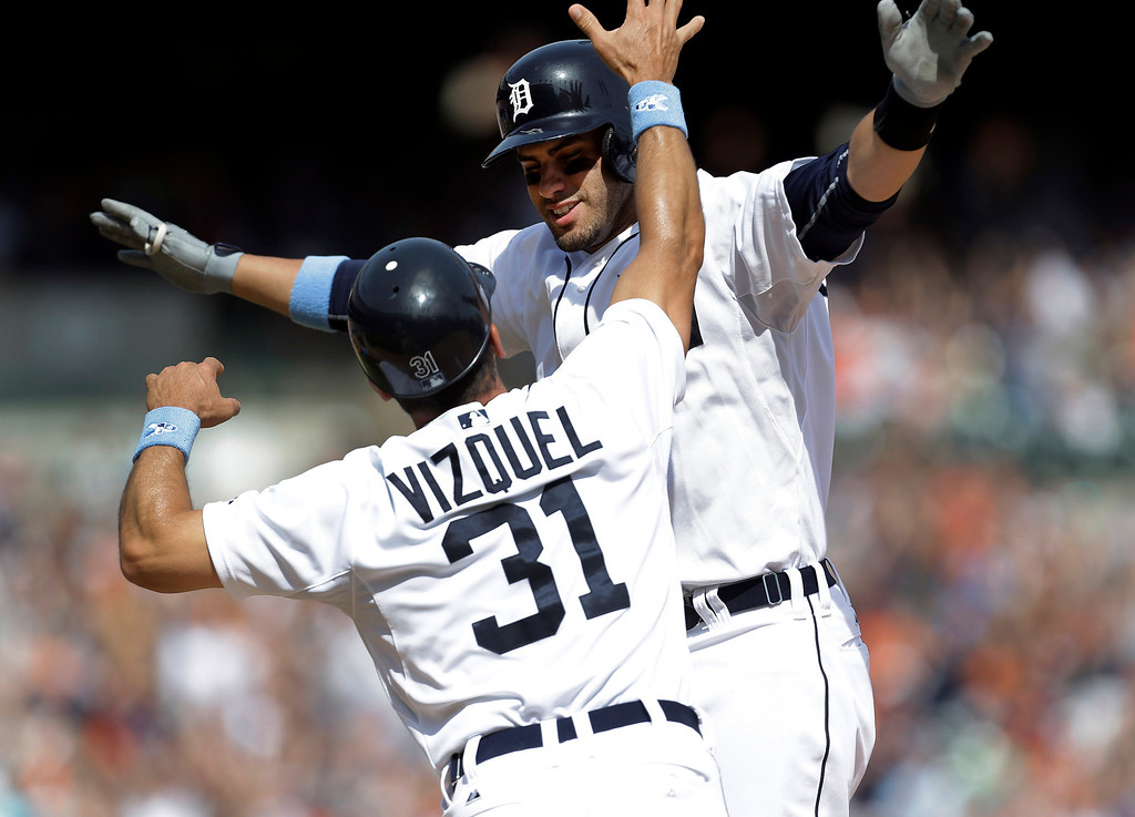 . Detroit Tigers\' J.D. Martinez, top, celebrates with first base coach Omar Vizquel (31) after hitting a walkoff sacrifice fly, scoring Torii Hunter, against the Minnesota Twins in the ninth inning of a baseball game in Detroit, Sunday, June 15, 2014. Detroit won 4-3. (AP Photo/Paul Sancya)