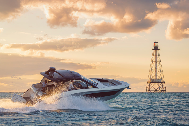 2021-Sundancer-370-Outboard-DAO370-lifestyle-starboard-stern-three-quarter-couple-lighthouse-00747.jpg