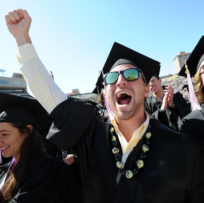 . Chris Nicholls, an Environmental Design graduate, cheers on his school during the 2013 University of Colorado Spring Commencement on Friday. (Cliff Grassmick/Daily Camera)