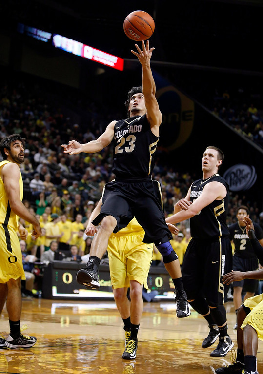 . Colorado\'s Sabatino Chen (23) drives to the basket as Oregon defender Arsalan Kazemi, left, watches during the first half of Colorado\'s game against Oregon in an NCAA college basketball game at Matthew Knight Arena in Eugene, Ore. Thursday, Feb. 7, 2013. (AP Photo/Brian Davies)