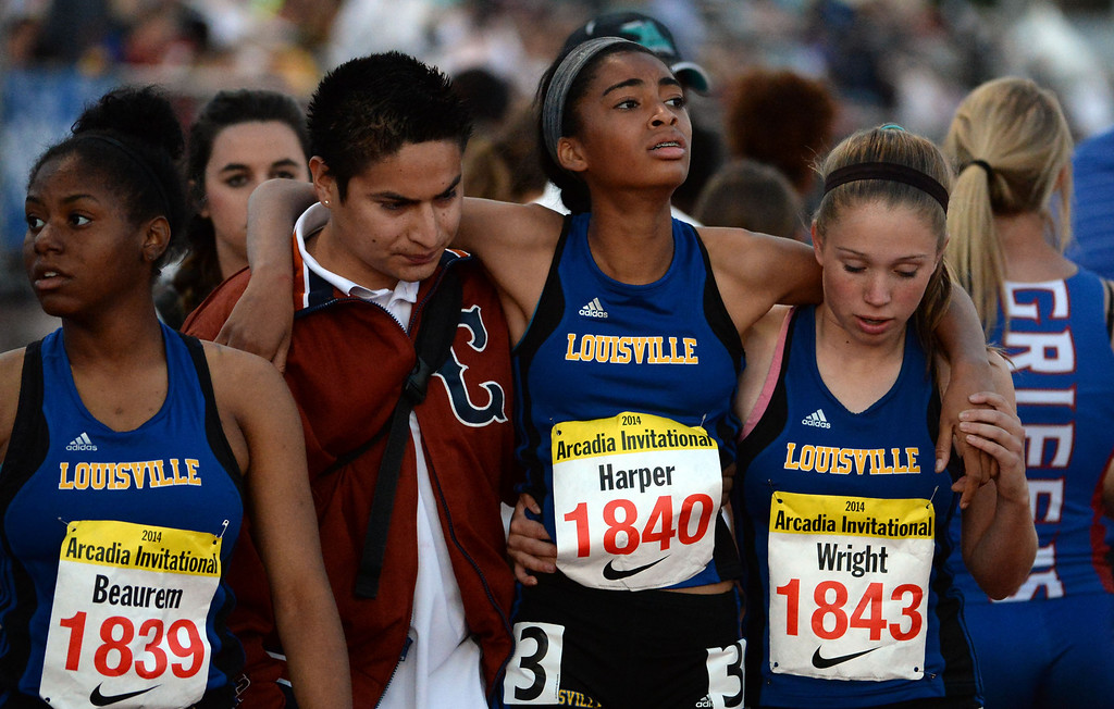 . Louisville\'s Jayla Harper is helped by teammates after competing in the 800 sprint Medley Invitational during the Arcadia Invitational track and field meet at Arcadia High School in Arcadia, Calif., on Friday, April 11, 2014.  (Keith Birmingham Pasadena Star-News)