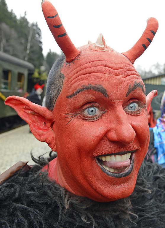 . A man costumed as a devil pose in front of a small train in Schierke, central Germany, Tuesday, April 30, 2013. Hundreds of costumed devils and witches meet to celebrate Walpurgis Night, a traditional religious holiday of pre-Christian origins. The event is named after St. Walburga, an English nun who helped convert the Germans to Christianity in the 8th century. (AP Photo/Jens Meyer)