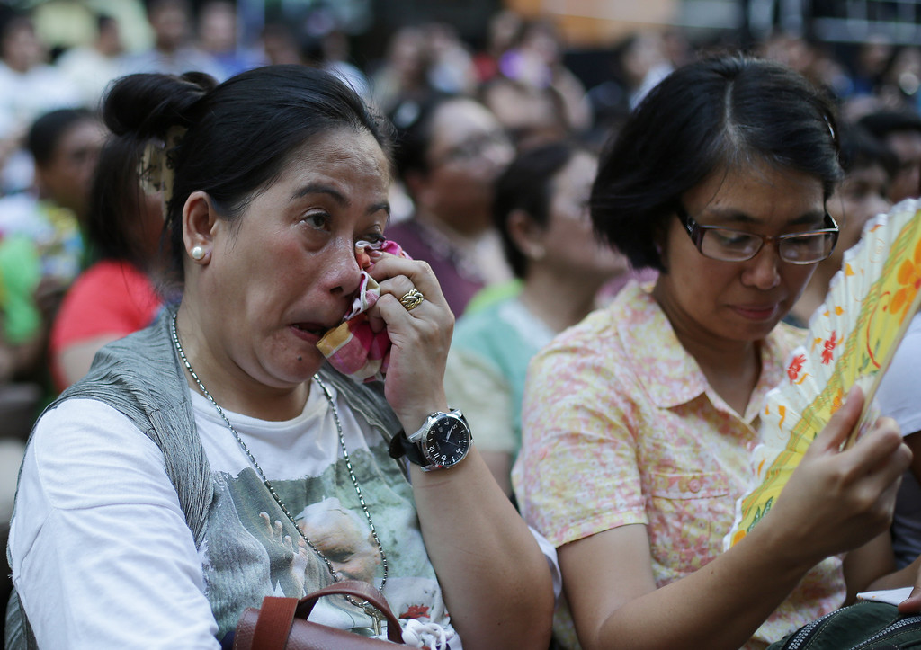 . A Filipino devotee wipes tears as she watches the live satellite broadcast of the canonization or the elevation to sainthood in the Vatican of Roman Catholic Pope John Paul II and Pope John XXIII on Sunday, April 27, 2014 in suburban Quezon city, north of Manila, Philippines. Pope Francis declared his two predecessors John XXIII and John Paul II saints on Sunday before hundreds of thousands of people in St. Peter\'s Square, an unprecedented ceremony made even more historic by the presence of retired Pope Benedict XVI. The predominantly Roman Catholic Philippines joins several nations worldwide in the celebration of canonization of the two Popes. (AP Photo/Aaron Favila)