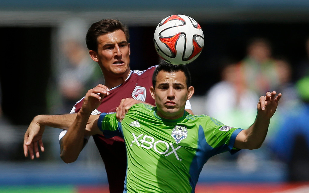 . Seattle Sounders\' Marco Pappa, right, and Colorado Rapids\' Thomas Piermayr, left, battle for a header, Saturday, April 26, 2014, in the first half of an MLS soccer match in Seattle. (AP Photo/Ted S. Warren)