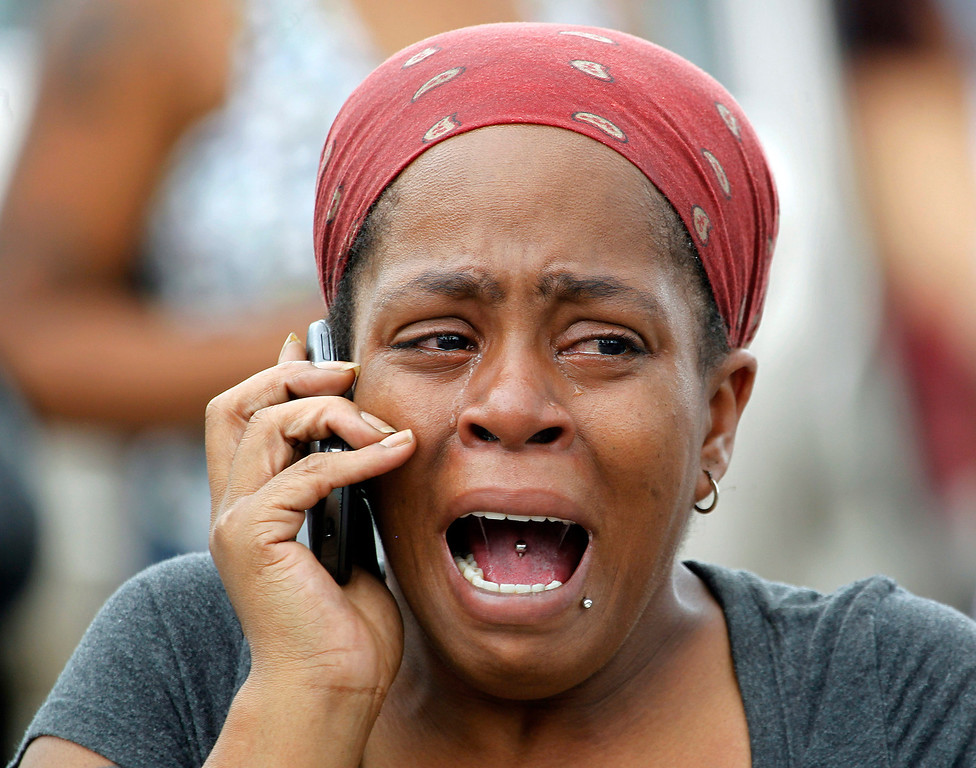 . Nicole Webb cries as she talks on a phone in the parking lot of a store while waiting for her 9-year-old son, a student at Ronald E. McNair Discovery Learning Academy in Decatur, Ga., on Tuesday, Aug. 20, 2013. Superintendent Michael Thurmond says all students at the school east of Atlanta are accounted for and safe and that he is not aware of any injuries. (AP Photo/John Bazemore)