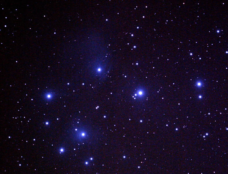 Messier M45 Pleiades, Seven Sisters, Subaru or Matariki - 14/11/2010 (Processed RAW stack)  One of the most well known of open clusters, the Pleiades or Seven Sisters, located in Taurus at ~400 Light Years distance is amongst the nearest star clusters to Earth. It is the most obious cluster to the naked eye. It has been named in many ancient cultures. The cluster is dominated by hot blue and extremely luminous stars that have formed within the last 100 million years. Dust that forms a faint reflection nebulosity around the brightest stars was thought at first to be left over from the formation of the cluster, but is now known to be an unrelated dust cloud in the interstellar medium that the stars are currently passing through.  First use of RAW (CR2) images and Darks on this object. Compare to JPEG stack on 31/10/2010. Also compare to a reprocessing of this stack in 2012.  DeepSkyStacker 3.3.2 Stacked 70% of 8 Images ISO 800 120 Sec, 3 DARK, 5 BIAS, 0 FLATS, Post-processed by Photoshop CS3.   Things to note is the slightly excessive blue processing and that the nebulosity is very tenuous and over-processed to have it show clearly. The use of Dark frames has reduced the hot pixels.  Limited cropping is possible due to the size of this object so some spherical aberration is evident near the outer edges of the image. Focused using a Bahtinov Mask.    Telescope - Apogee OrthoStar LOMO 80/480 with Hotech SCA T-Adapter, Hutech IDAS LPS-P2 filter, Canon 400D DSLR, Ambient xxC (not recorded). Mount - Skywatcher NEQ6 Pro. Guidescope - Orion ShortTube 80 with Star Shoot Auto Guider.