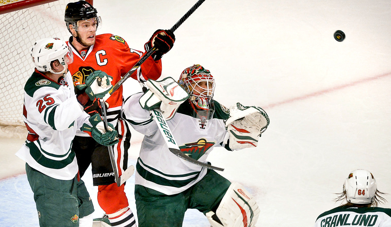 . Minnesota goalie Ilya Bryzgalov keeps his eyes on the puck as teammate Jonas Brodin and Chicago\'s Jonathan Toews battle for position during the first period.  (Pioneer Press: Ben Garvin)