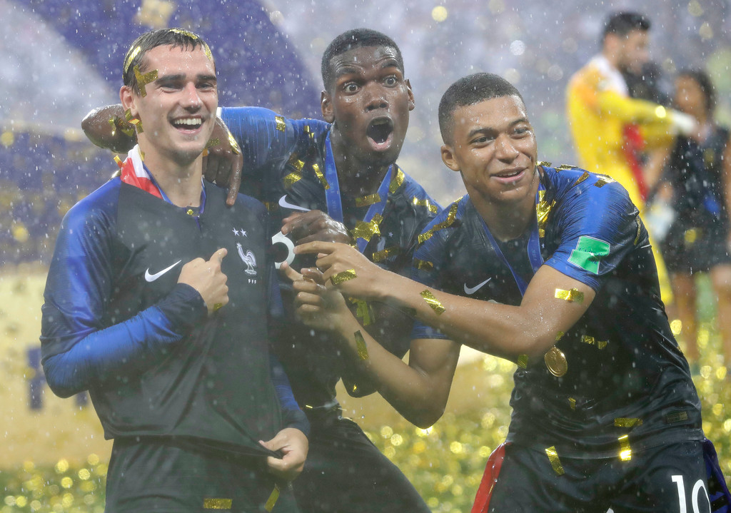 . France\'s Antoine Griezmann, points to two stars on his jersey indicating two world cup wins, as he celebrates with Paul Pogba and Kylian Mbappe after the final match between France and Croatia at the 2018 soccer World Cup in the Luzhniki Stadium in Moscow, Russia, Sunday, July 15, 2018. France won the final 4-2. (AP Photo/Matthias Schrader)