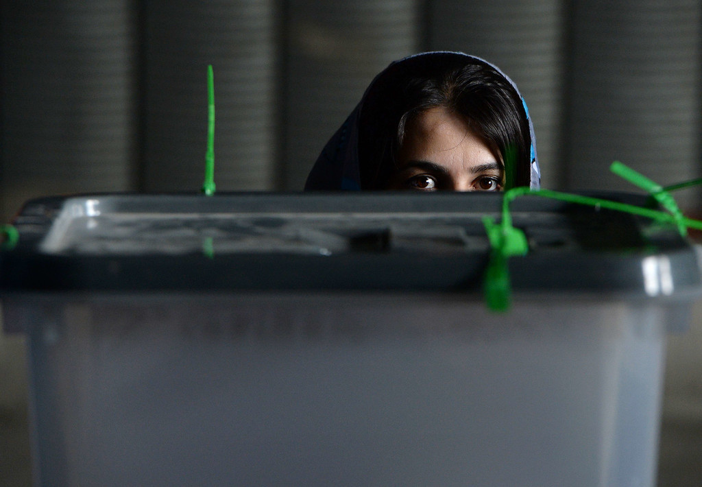 . An Afghan election commission worker waits prior to the opening of the seals to a box containing ballot papers for an audit of the presidential run-off votes at a counting centre in Kabul on July 17, 2014.  Afghanistan on July 17 began a massive audit of 8.1 million ballots cast in the run-off round of its controversial presidential vote, hours after a brazen Taliban raid on Kabul\'s airport. The audit is aimed at reversing a destabilizing political crisis that has threatened to widen the country\'s ethnic fissures as NATO winds down its deployment after more than a decade of war. AFP PHOTO/Wakil KOHSAR/AFP/Getty Images