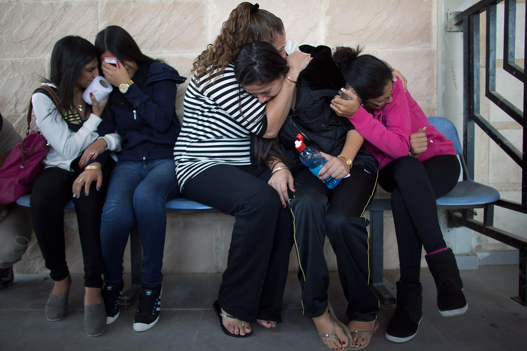 . Relatives take cover during a rocket attack during the funeral for Itzik Amsalem, 49, one of the three people who died in a rocket attack on November 16, 2012 in Kiryat Malachi, Israel. Three people were killed in Israel November 15, after a building was hit by a rocket fired from the Hamas-ruled Gaza Strip. Palestinian rocket attacks followed a series aerial strikes on targets in Gaza launched by Israeli Defense Forces (IDF) which killed a top military commander of Hamas.  (Photo by Uriel Sinai/Getty Images)