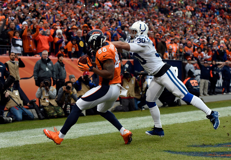 . Demaryius Thomas (88) of the Denver Broncos pulls in the ball scoring the Broncos first touchdown halfway through the first quarter with pressure from LaRon Landry (30) of the Indianapolis Colts.  The Denver Broncos played the Indianapolis Colts in an AFC divisional playoff game at Sports Authority Field at Mile High in Denver on January 11, 2015. (Photo by Tim Rasmussen/The Denver Post)