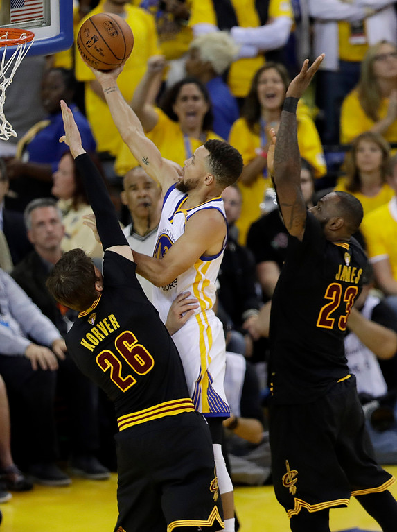 . Golden State Warriors guard Stephen Curry shoots between Cleveland Cavaliers guard Kyle Korver (26) and forward LeBron James (23) during the second half of Game 5 of basketball\'s NBA Finals in Oakland, Calif., Monday, June 12, 2017. (AP Photo/Marcio Jose Sanchez)