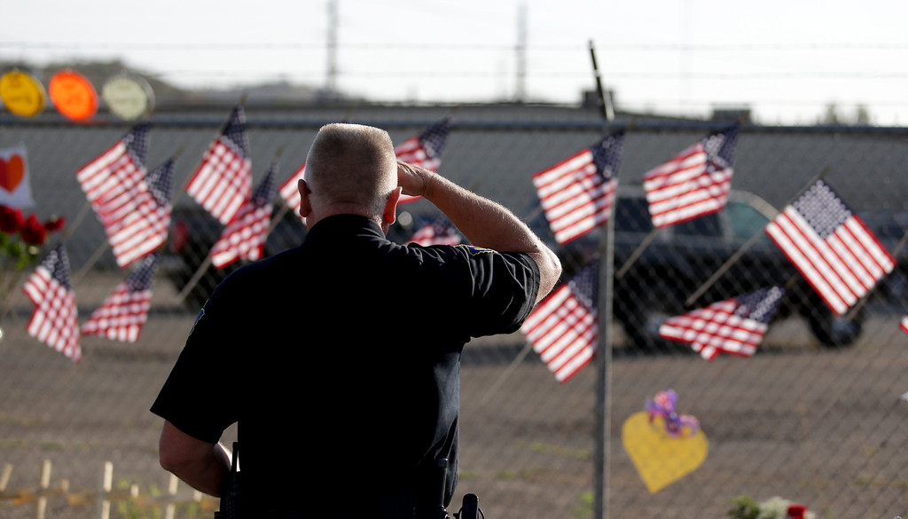 . George Murphy of the Yavapi Tribal Police pays his respects at a makeshift memorial outside the Granite Mountain Interagency Hotshot Crew fire station, Tuesday, July 2, 2013,  in Prescott, Ariz., honoring 19 firefighters killed battling a wildfire near Yarnell, Ariz., Sunday. (AP Photo/Chris Carlson)
