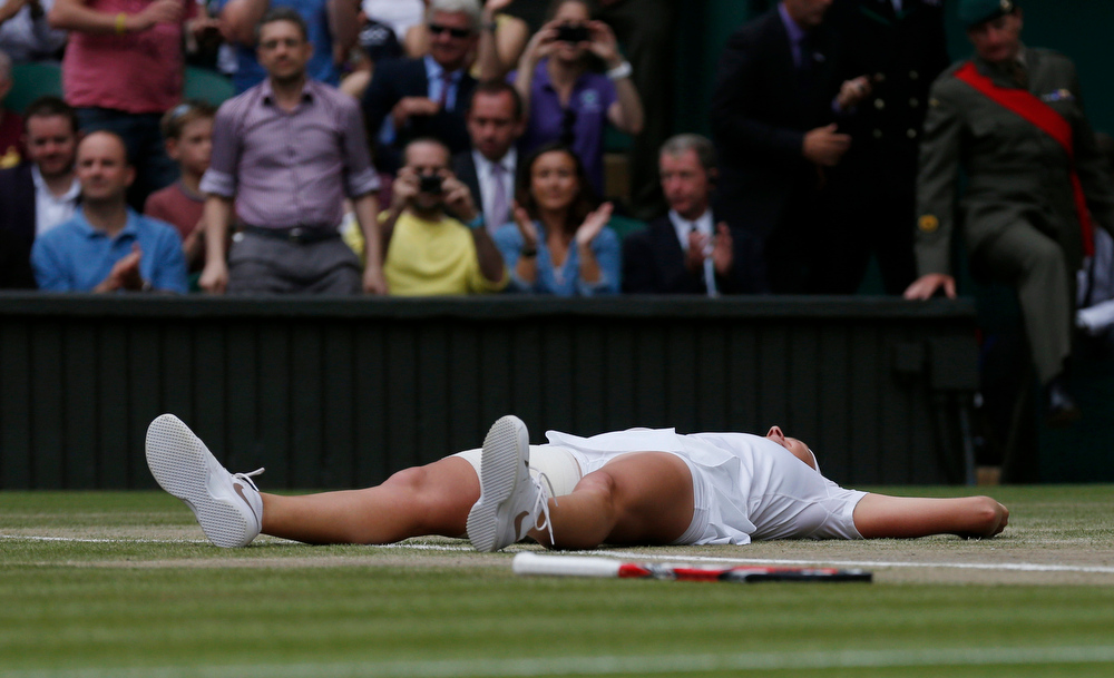 Description of . Petra Kvitova of Czech Republic lays on the court as she celebrates defeating Eugenie Bouchard of Canada in their women's singles final at the All England Lawn Tennis Championships in Wimbledon, London, Saturday July 5, 2014. (AP Photo/Sang Tan)