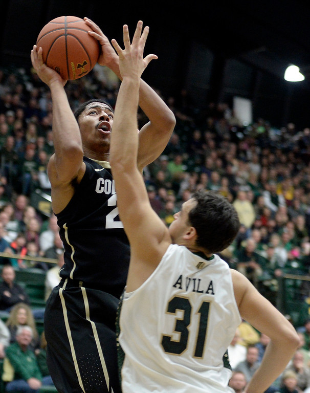 . University of Colorado\'s Spencer Dinwiddie takes a shot over J.J. Avila during an NCAA game against Colorado State University on Tuesday, Dec. 3, 2013, at the Moby Arena in Fort Collins. Jeremy Papasso/ Camera