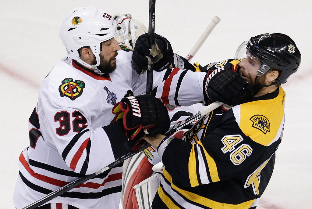 . Chicago Blackhawks defenseman Michal Rozsival (32), of the Czech Republic, and Boston Bruins center David Krejci (46), of the Czech Republic, tangle during the third period in Game 6 of the NHL hockey Stanley Cup Finals, Monday, June 24, 2013, in Boston. (AP Photo/Charles Krupa)