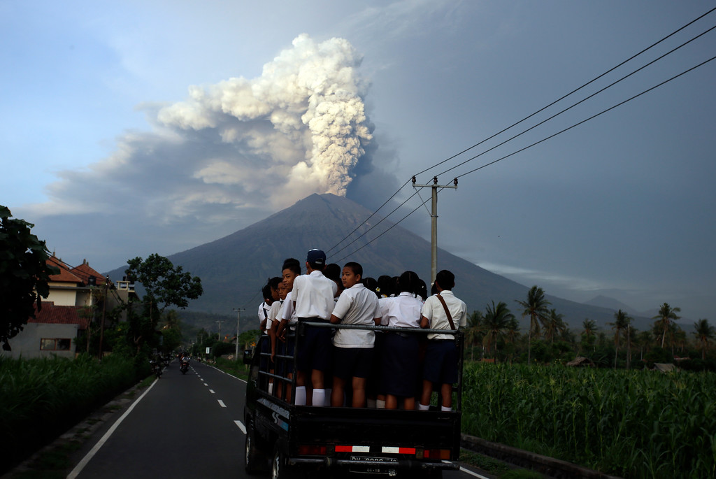 . School students stand on a truck as their transport to go to school with the Mount Agung volcano spews smoke and ash in Karangasem, Bali, Indonesia, Tuesday, Nov. 28, 2017. Indonesia authorities raised the alert for the rumbling volcano to highest level on Monday and closed the international airport on the tourist island of Bali stranding some thousands of travellers.(AP Photo/Firdia Lisnawati)