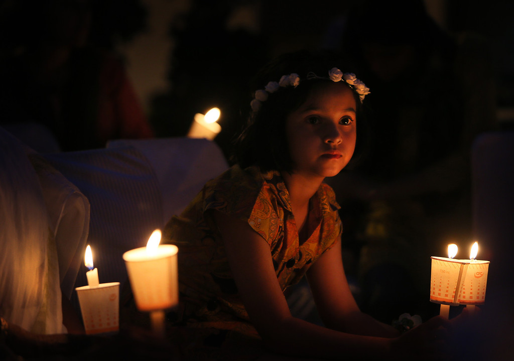 . An Indian girl holds a candle during an awareness campaign by Greenpeace activists to save Mahan forest in the Indian state of Madhya Pradesh, on Earth Day in New Delhi, India, Tuesday, April 22, 2014. Greenpeace activists claim that Mahan forest, with villages dependent on its non-timber forest produce, is being threatened with the prospect of coal mining by giant corporations. (AP Photo/Manish Swarup)