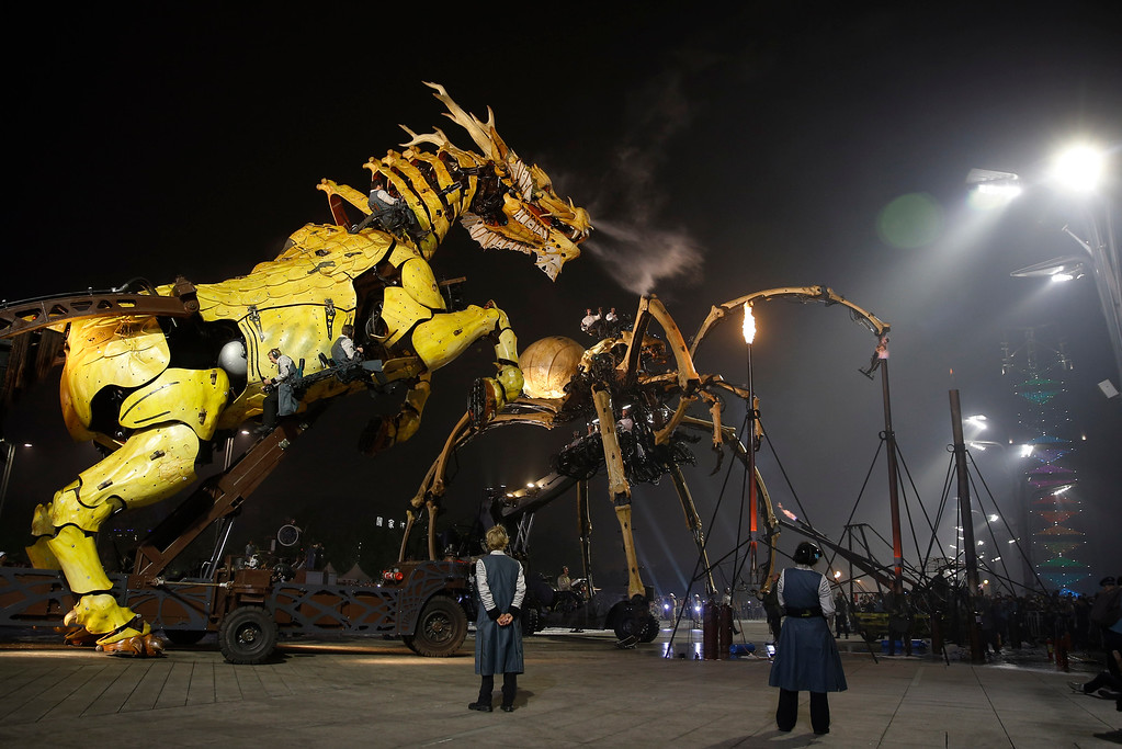 """. French production company La Machine\'s latest creation \""""the Long Ma\"""" or Dragon Horse, left, and the mechanical spider also known as La Princesse perform in front of the Bird\'s Nest Stadium in Beijing, China Sunday, Oct. 19, 2014. The performance, which attended by French Foreign Minister Laurent Fabius and his Chinese counterpart Wang Yi, mark the climax of celebrations for the 50th anniversary of Sino-French diplomatic relations. (AP Photo/Andy Wong)"""