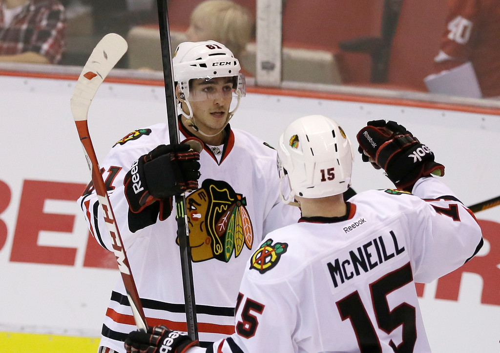 . Chicago Blackhawks left wing Garret Ross (61) is congratulated by teammate Mark McNeill after scoring during the third period of an NHL hockey game against the Detroit Red Wings in Detroit, Thursday, Sept. 25, 2014. (AP Photo/Carlos Osorio)