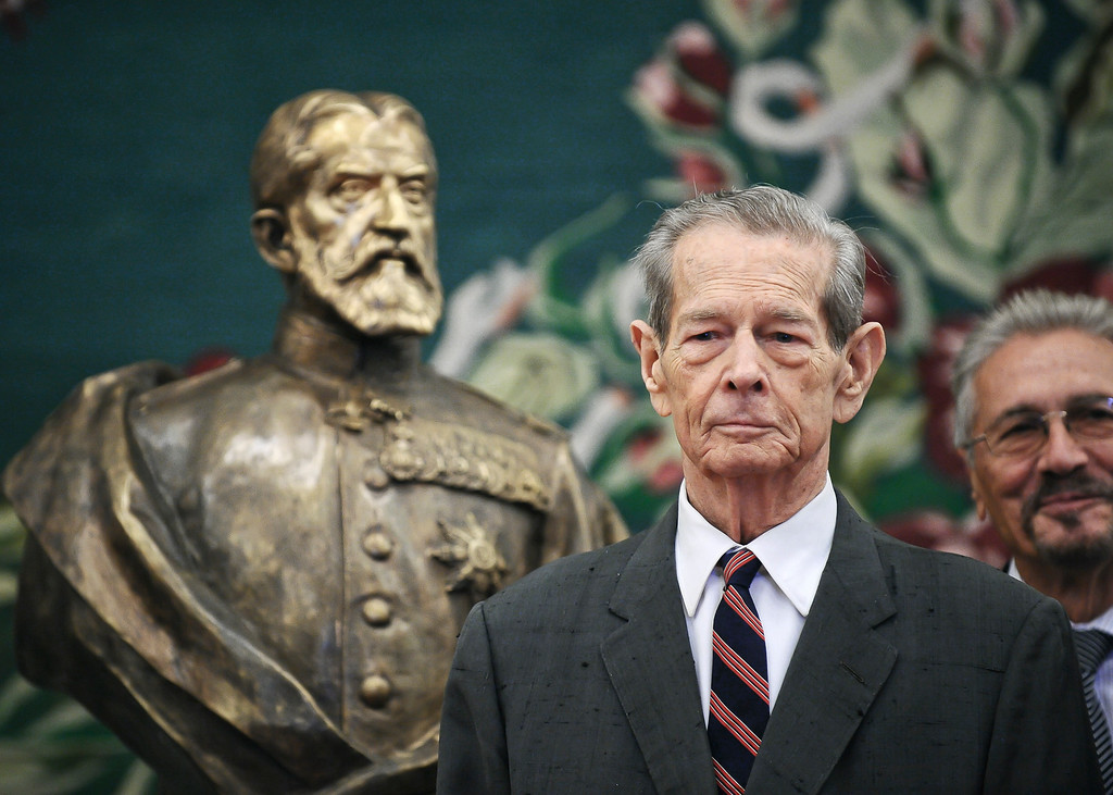 . FILE - In this Tuesday, Oct. 25, 2011, file photo, former Romanian King Michael poses next to a bronze sculpture depicting the founder of Romania\'s royal dynasty, King Carol I, in the country\'s parliament in Bucharest, Romania. Romania\'s royal house says former King Michael, who ruled Romania during WWII, has died, Tuesday, Dec. 5, 2017, in Switzerland aged 96. (AP Photo/Octav Ganea, File)