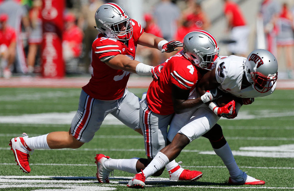 . Ohio State defenders Tuf Borland, left, and Jordan Fuller, center, tackle UNLV wide receiver Kendal Keys during the first half of an NCAA college football game Saturday, Sept. 23, 2017, in Columbus, Ohio. (AP Photo/Jay LaPrete)