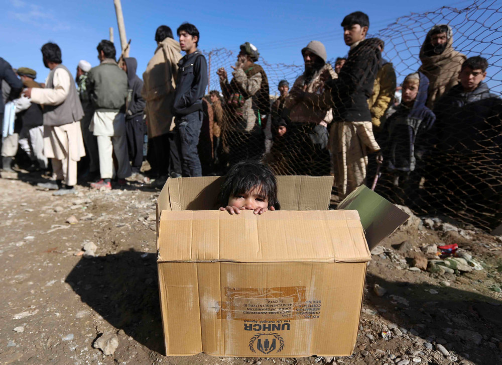 Description of . An internally displaced Afghan girl sits inside a box as she waits for the distribution of winter assistance in Kabul December 23, 2012. The United Nations High Commissioner for Refugees (UNHCR) began a winter assistance programme for returnees from Pakistan and Iran, internally displaced persons and others who are at risk in the cold weather. REUTERS/Omar Sobhani