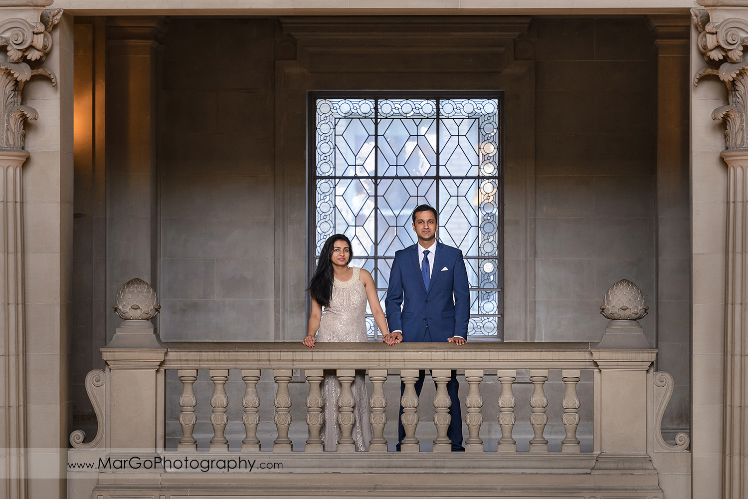 woman in beige dress and man in navy blue suit on the balcony on the third floor of San Francisco City Hall