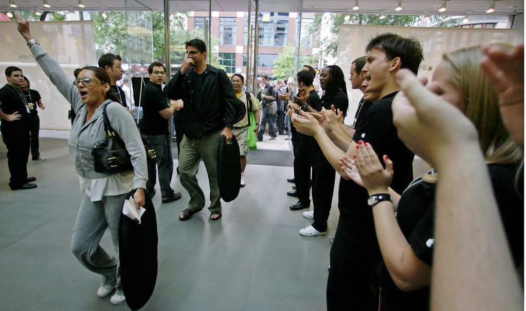 . Employees applaud as customers rush into the Apple Store in downtown Chicago Friday, June 29, 2007, to purchase the company\'s new Apple  iPhone, a gadget that combines the functions of a cell phone, iPod media player and wireless Web browser.  Apple is banking on the new do-everything phone with a touch-sensitive screen to become its third core business next to its moneymaking iPod players and Macintosh computers. (AP Photo/M. Spencer Green)