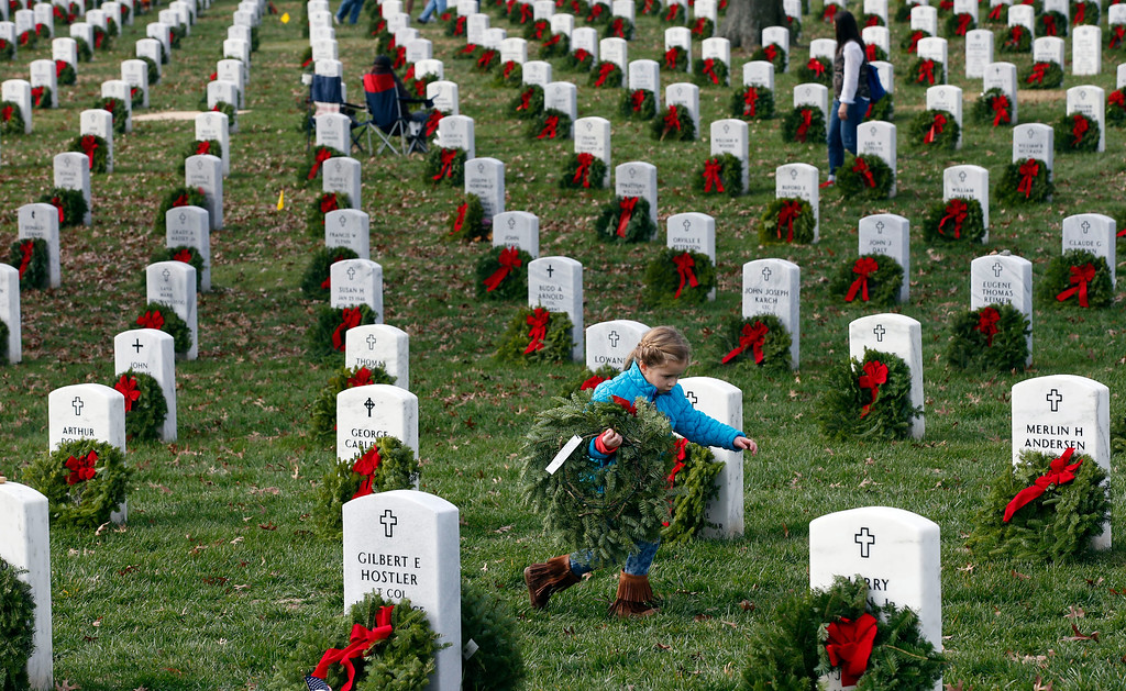 . Lane Austin, 6, of Virginia Beach, Va., carries a wreath to grave during Wreaths Across America at Arlington National Cemetery, Saturday, Dec. 12, 2015 in Arlington, Va. Organizers estimated that volunteers placed 240,815 wreaths at Arlington.(AP Photo/Alex Brandon)
