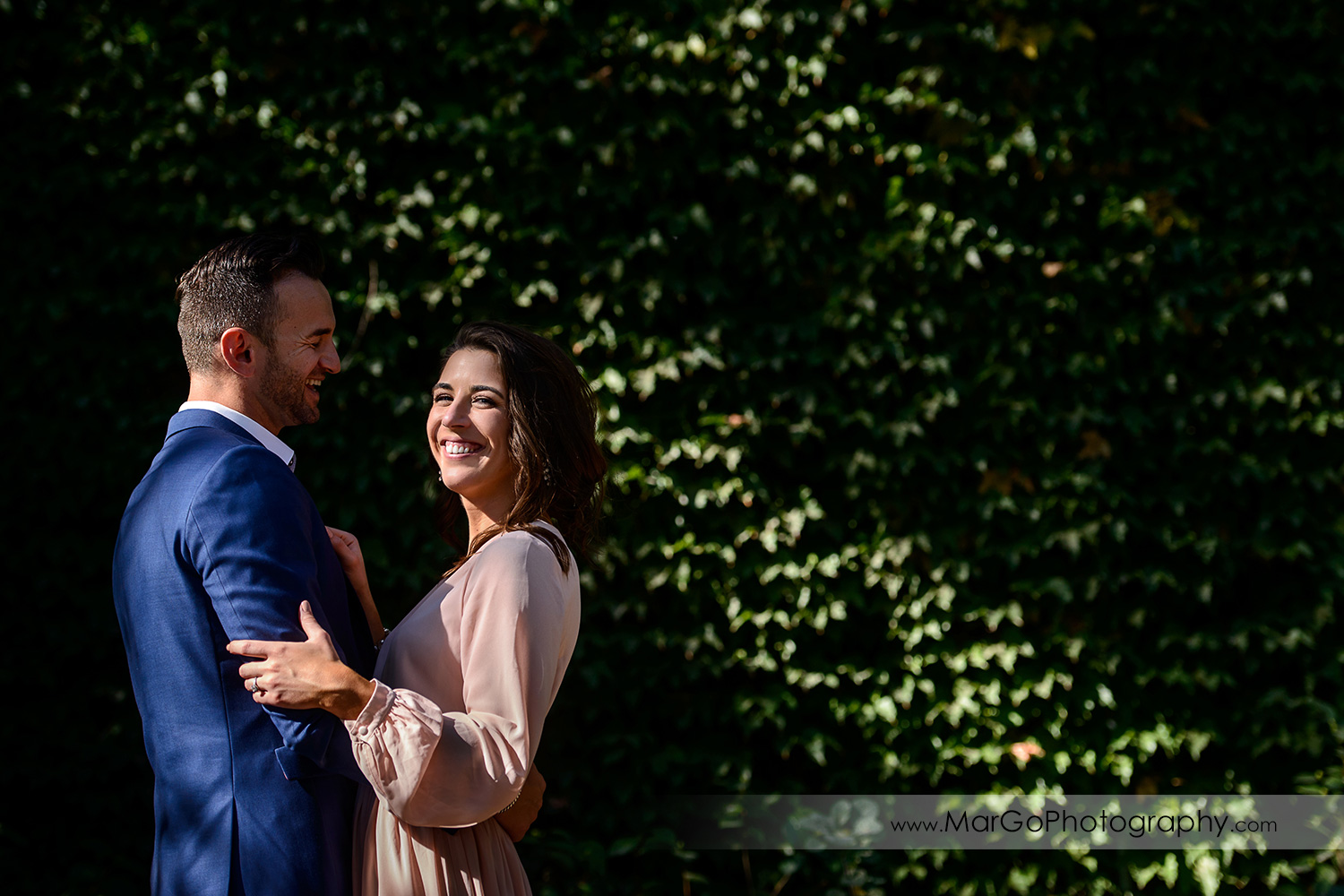 man in blue suit and woman in pink dress dancing in front of green wall during Napa Valley engagement session at Frank Family Vineyards in Calistoga