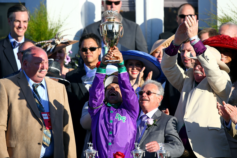 Description of . Jockey Victor (C) Espinoza celebrates with the trophy in the winners circle after guiding California Chrome #5 to win the 140th running of the Kentucky Derby at Churchill Downs on May 3, 2014 in Louisville, Kentucky.  (Photo by Andy Lyons/Getty Images)