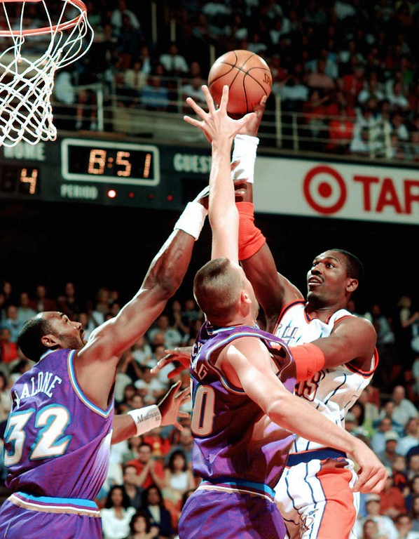. Houston Rockets\'  Hakeem Olajuwon (34) shoots over Utah Jazz\'s Karl Malone (32) and Greg Ostertag (00) during the first quarter in Game 6 of the Western Conference Finals Thursday, May 29, 1997, in Houston. (AP Photo/Pat Sullivan)