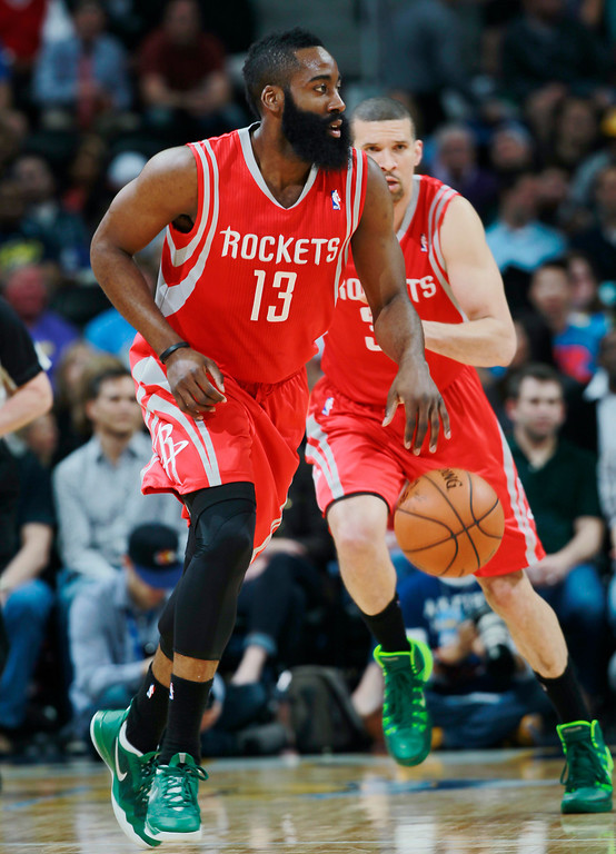 . Houston Rockets guard James Harden, front, picks up a loose ball as guard Francisco Garcia, of the Dominican Republic, follows against the Denver Nuggets in the first quarter of an NBA basketball game in Denver on Wednesday, April 9, 2014. (AP Photo/David Zalubowski)