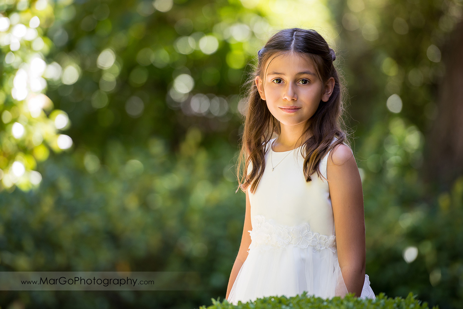portrait of first communion girl in white dress at green background at Cafe Wisteria in Menlo Park