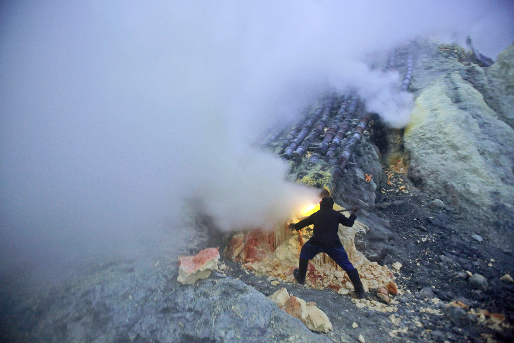 . In this Saturday, April 16, 2016 photo, miner dig out sulfur slabs at the crater of Mount Ijen in Banyuwangi, East Java, Indonesia. The workers started to work just after midnight in order to finish early in the morning to avoid having to work under the hot tropical sun. (AP Photo/Binsar Bakkara)