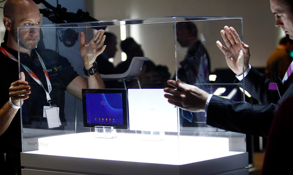 . Employees place a protective case around the Sony Xperia Z2 during a press conference at the Mobile World Congress in Barcelona, on February 24, 2014.  The Mobile World Congress runs from the 24 to 27 February where participants and visitors alike can attend conferences, network, discover cutting-edge products and technologies at among the 1,700 exhibitors as well as seek industry opportunities and make deals.  QUIQUE GARCIA/AFP/Getty Images