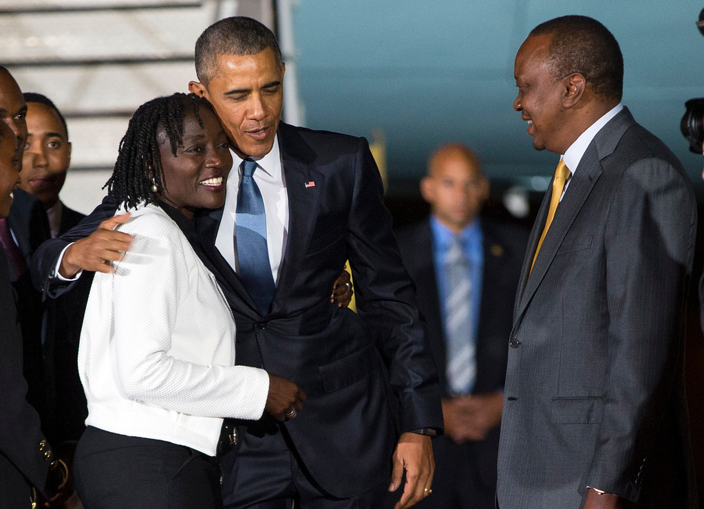 . Kenyan President Uhuru Kenyatta, right, watches as President Barack Obama, center, hugs his half-sister Auma Obama, after he arrived at Kenyatta International Airport, on Friday, July 24, 2015, in Nairobi, Kenya. Obama is traveling on a two-nation African tour where he will become the the first sitting U.S. president to visit Kenya and Ethiopia. (AP Photo/Evan Vucci)