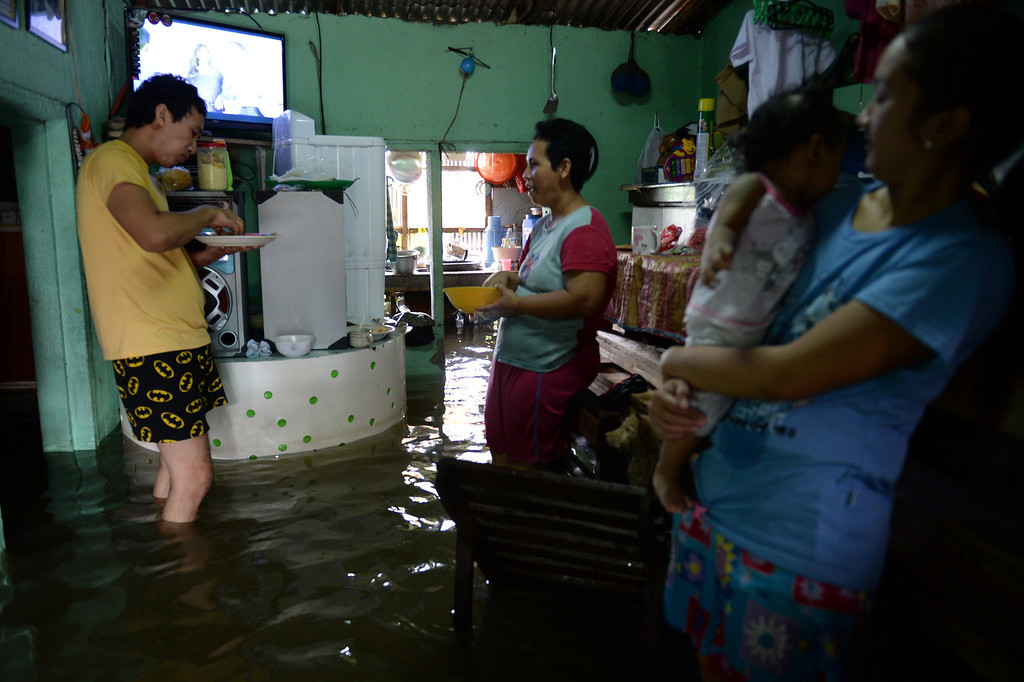 . Residents affected by flooding due to heavy rains exarcebated by Tropical storm Trami eat inside their flooded home in the town of Calumpit, Bulacan province, north of Manila on August 22, 2013. Disaster-weary Philippine residents mopped up August 22 after four days of rains that officials said had killed 18 people and forced more than half a million from flooded homes. TED ALJIBE/AFP/Getty Images