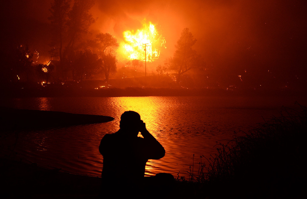 . A local resident looks at his neighbor\'s two-story house fully involved in fire as the Powerhouse Fire entered a fourth day early Sunday, June 2, 2013, in the Angeles National Forest near the Lake Hughes area. (Gene Blevins/L.A. Daily News)
