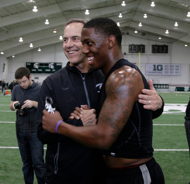 . Former Michigan State cornerback Darqueze Dennard, right, greets Michigan State coach Mark Dantonio after running drills during pro day for NFL scouts, Tuesday, March 11, 2014, in East Lansing, Mich. (AP Photo/Al Goldis)