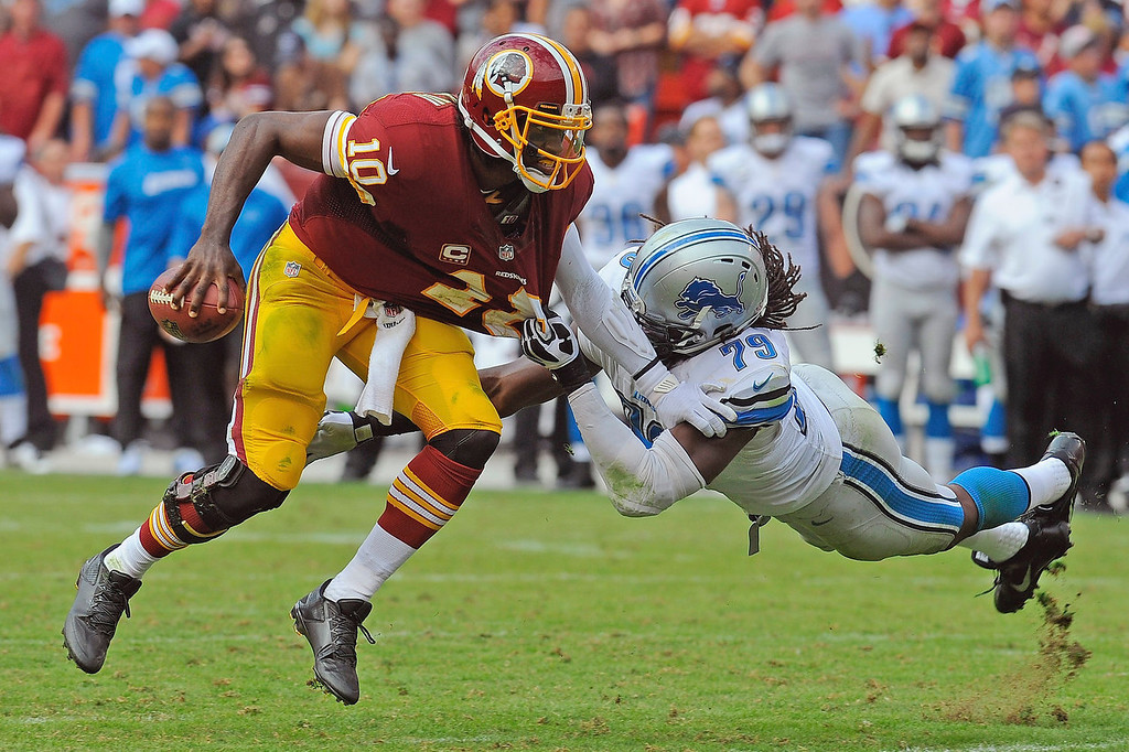 . Detroit Lions defensive end Willie Young gets a hand full of Washington Redskins quarterback Robert Griffin III\'s jersey during the second half of a NFL football game in Landover, Md., Sunday, Sept. 22, 2013. The Lions defeated the Redskins 27-20, breaking a 21-game losing streak to the Redskins at the Redskins home stadium. (AP Photo/Richard Lipski)