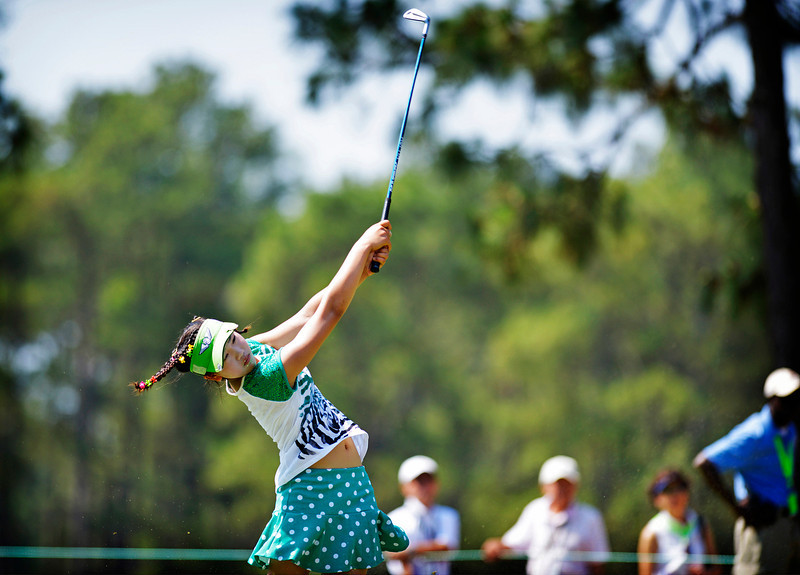 . Amateur Lucy Li, 11, hits from the fairway on the 15th hole during a practice round at the U.S. Women\'s Open golf tournament at Pinehurst No. 2, Tuesday, June 17, 2014, in Pinehurst, N.C. The sixth-grader from California is the youngest qualifier in the history of the U.S. Women\'s Open.  (AP Photo/The Fayetteville Observer, Abbi O\'Leary)