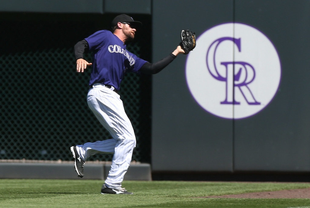 . Colorado Rockies right fielder Ben Paulsen catches sacrifice fly off the bat of San Francisco Giants\' Buster Posey in the first inning of a baseball game in Denver on Wednesday, Sept. 3, 2014. (AP Photo/David Zalubowski)
