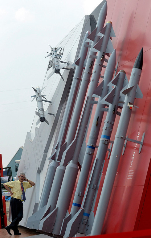 ". An official makes a phone call on his mobile phone while standing next to Rafael\'s missiles on display at the ""Aero India 2013\"" on the outskirts of the southern Indian city of Bangalore February 8, 2013. REUTERS/Stringer"