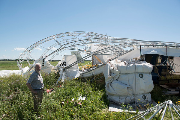 DAVID LIPNOWSKI / WINNIPEG FREE PRESS  President of Buoyant Aircraft Systems International Barry E. Prentice surveys damage to a hangar and two airships at St. Andrews airport Thursday July 21, 2016.