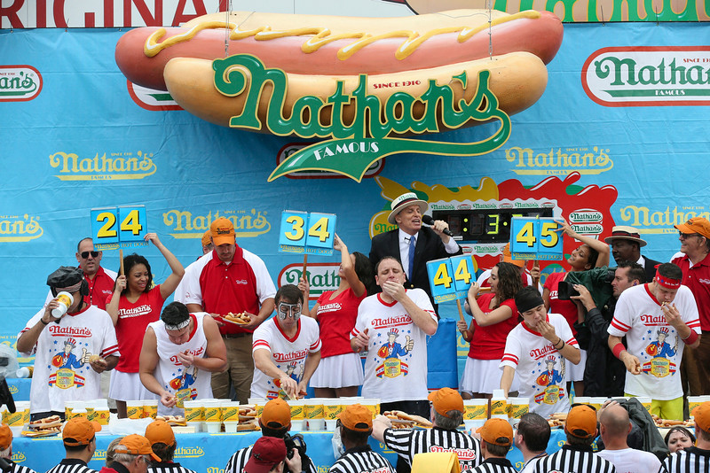 . Tim Janus, center left, Joey Chestnut, center right, and Matt Stonie, second from right, compete during the Nathan\'s Famous Fourth of July International Hot Dog Eating contest at Coney Island, Friday, July 4, 2014, in New York. Chestnut won his eighth contest by finishing 61 hotdogs and buns. (AP Photo/John Minchillo)