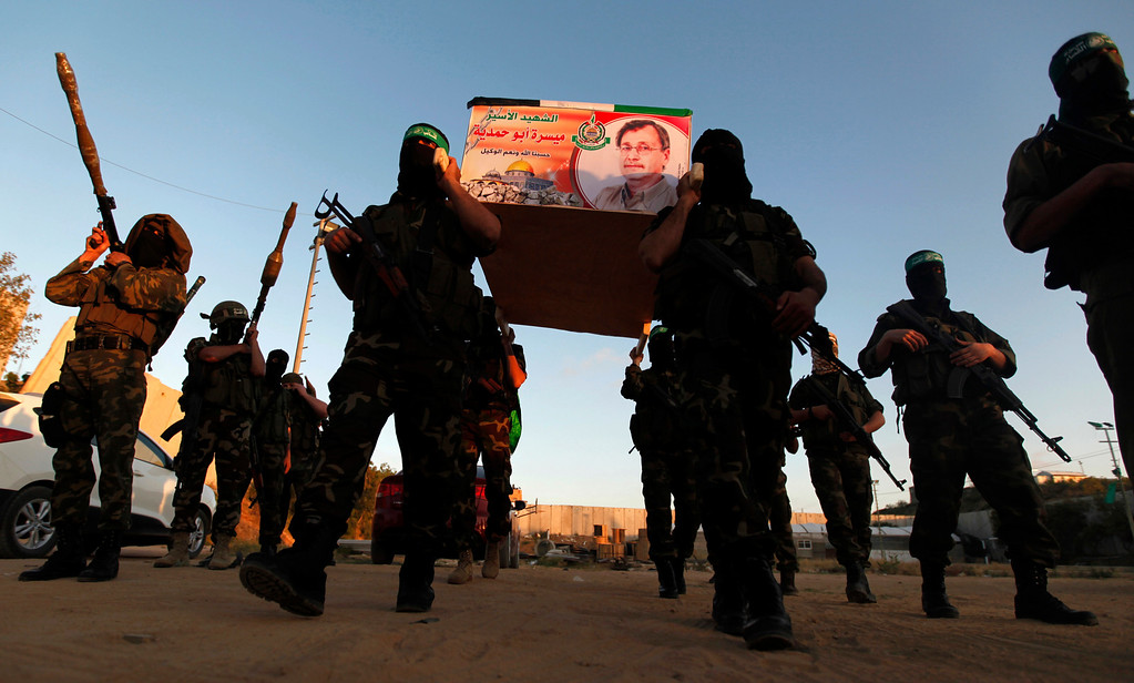 . Izzedine Al-Qassam Brigades militants carry a mock coffin of Maysara Abu Hamdiyeh in Gaza Strip, Tuesday, April 2, 2013. Abu Hamdiyeh, 64, who was serving a life sentence for his role in a foiled attempt to bomb a busy cafe in Jerusalem in 2002, died Tuesday of cancer in an Israeli jail. (AP Photo/Hatem Moussa)